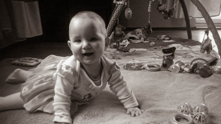radosne dziecko leży na brzuchu i się uśmiecha