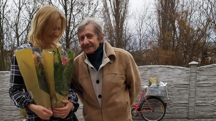 kobieta z kwiatami obok starszy mężczyzna
