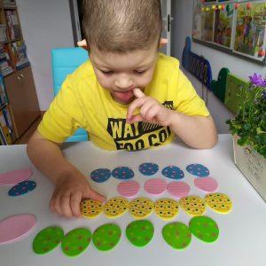 chłopiec układa piankowe jajka kolorowe w rzędach