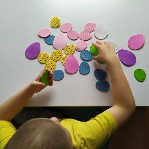 chłopiec układa piankowe jajka kolorowe